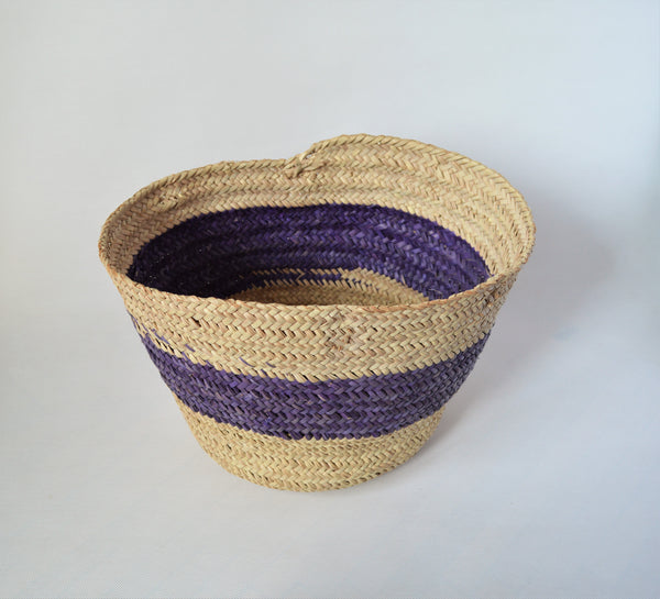 Round straw basket from natural palm leaves with a wide Purple stripe