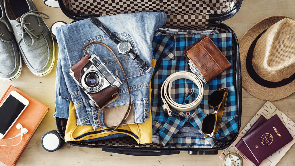 camera, clothes and suitcase packing for holiday