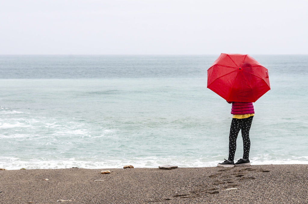 person standing on beach with umbrella