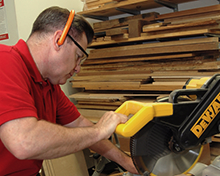 Woodworker using SensGard while sawing to protect hearing