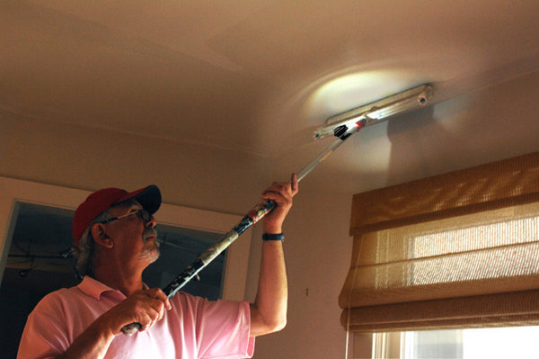 Using a Grip-On LED Hands-Free Flashlight attached to a paint-roller stick to light-up a dark ceiling