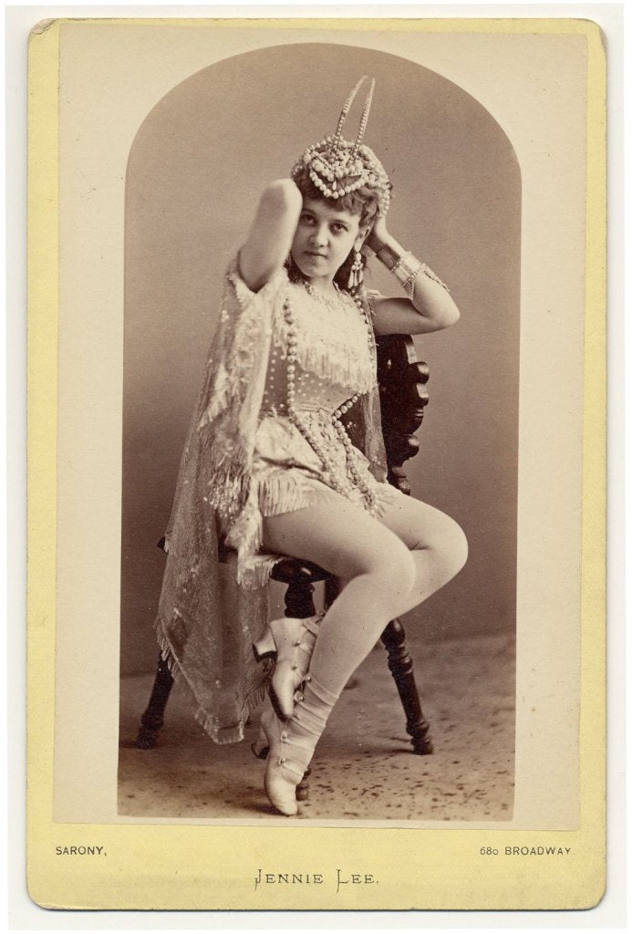 1890. Jennie Lee sitting on a chair,  holding a hair-dress on her head.