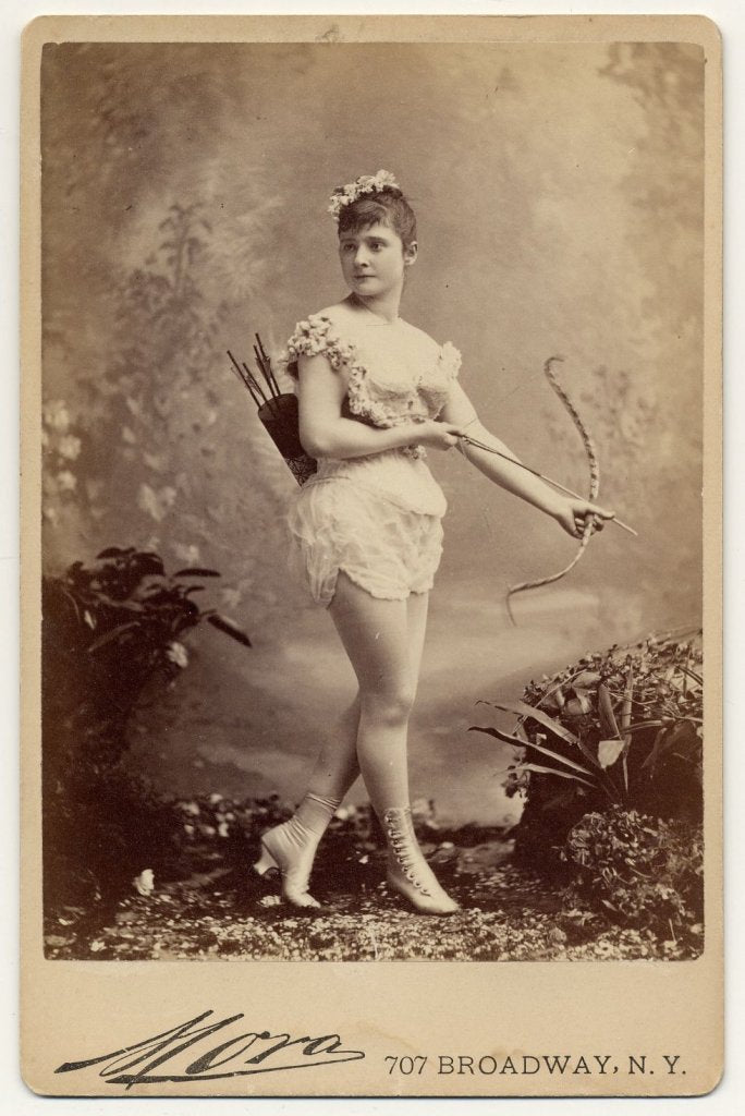 1890. Miss Farrington in short sleeveless costume, holding bow and arrow, with quiver and arrows on back, button heeled boots.