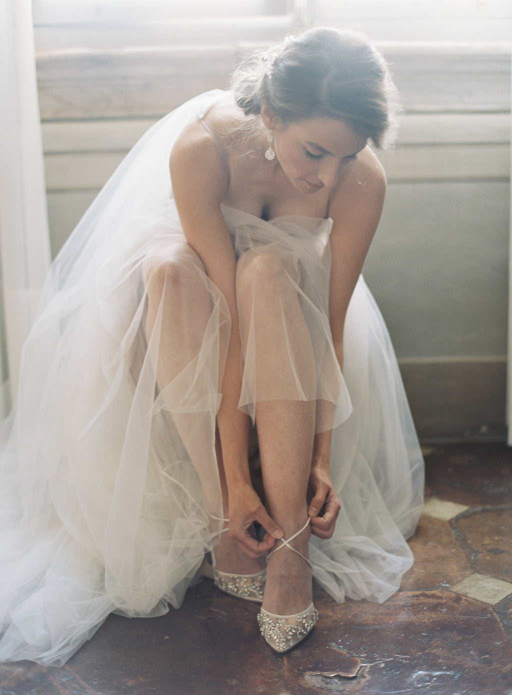 A bride sitting down to fix the lace on her wedding shoe.