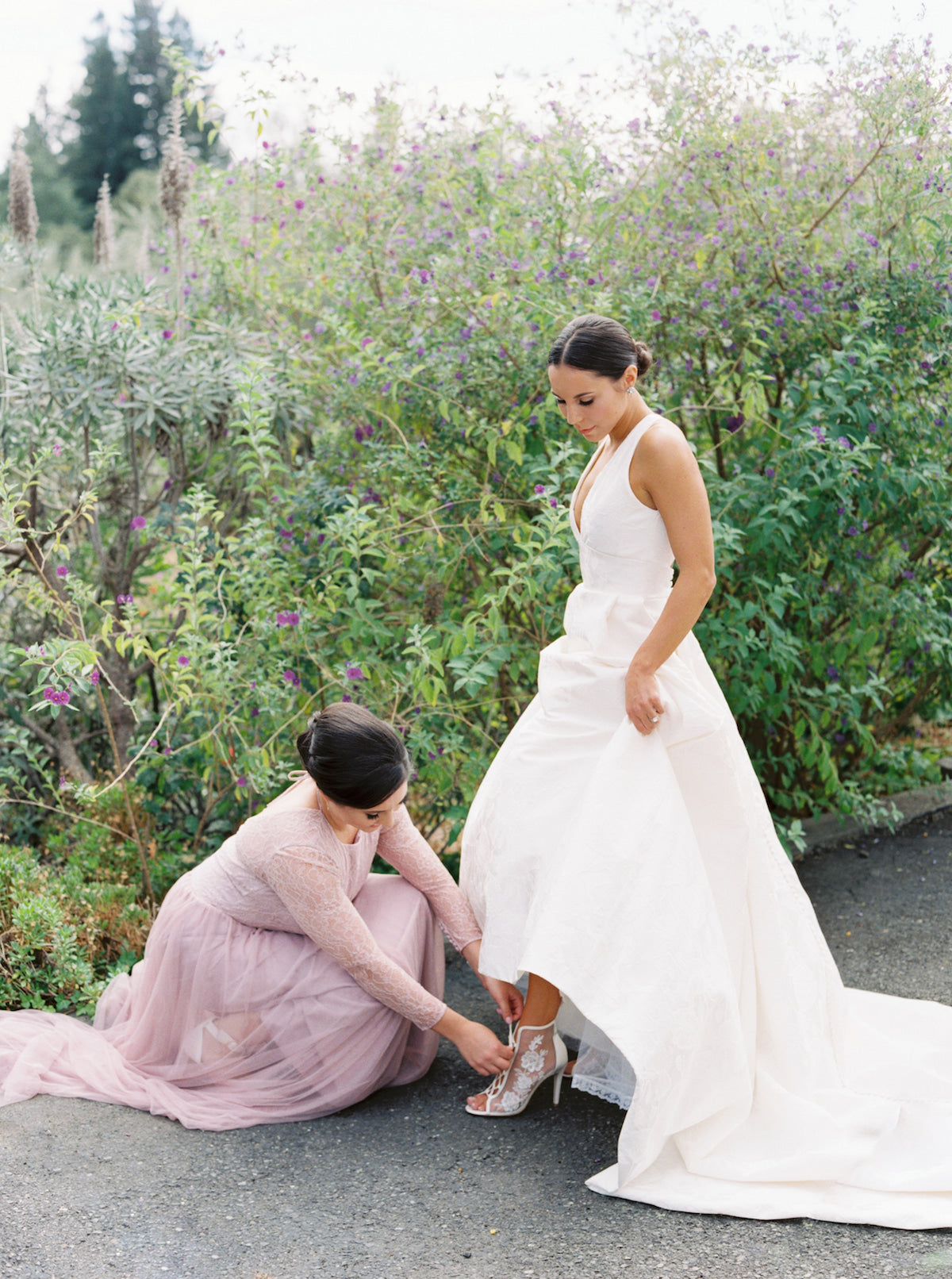 A bridesmaid helping a bride to put on her wedding shoe.