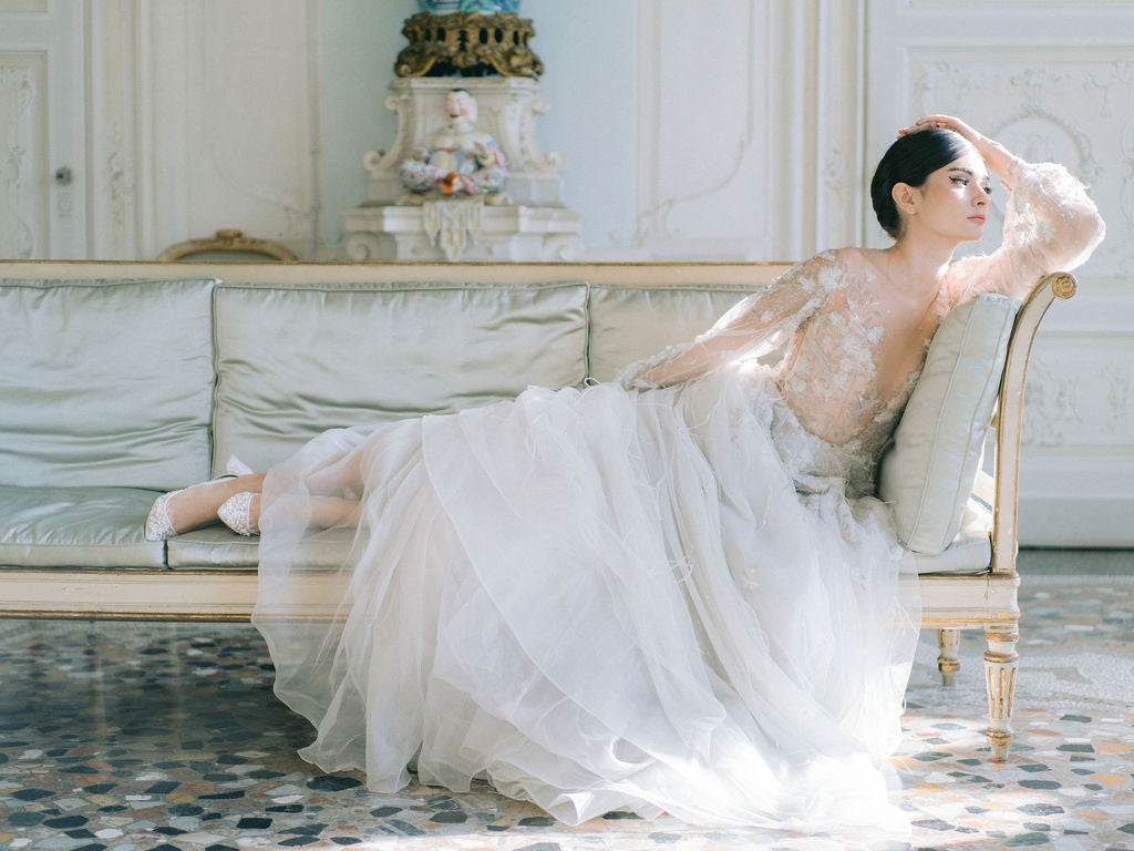 Model lounging in a designer wedding dress elegantly.