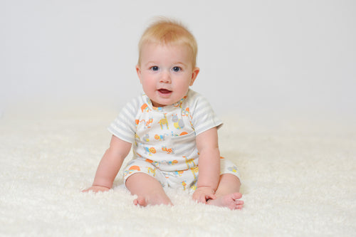 sitting baby with organic romper with safari animal print
