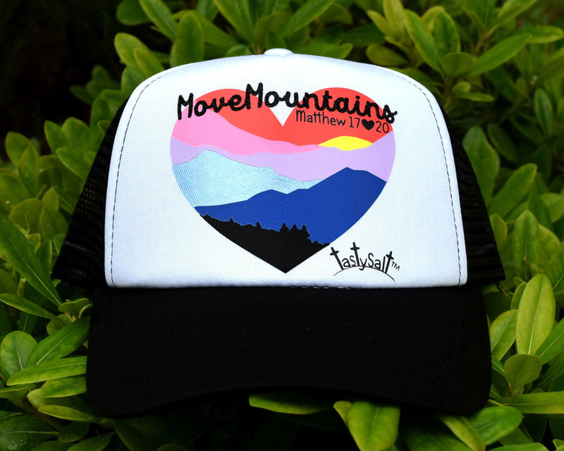 "Black and white women's Christian trucker hat. Handmade, hand pressed heart shaped landscape design of orange sky and bright setting sun upon bold silhouettes of cascading mountains in shiny Columbia blue, royal blue, lilac and soft pink behind a darkened tree line. ""Move Mountains"" scripted across the top."