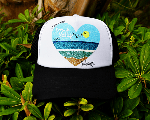 Black and white women's Christian trucker hat. Handmade, hand pressed design of white waves breaking beyond a shallow turquoise shore, washing up on glittery golden sand with aquamarine ocean and dark blue horizon. Sea birds silhouetted against bright blue shimmery sky and gleaming yellow sun.