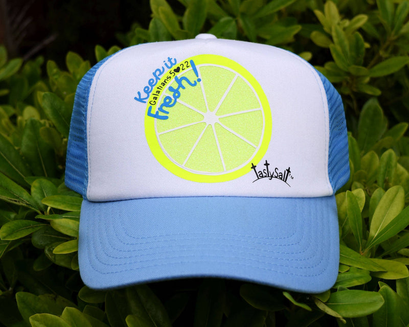 Light blue and white women's Christian trucker hat. Bright refreshing yellow lemon slice. Bright yellow rind, glittery neon yellow segments and white pith.