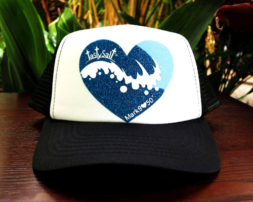 Black and white summer trucker hat. Handmade, hand pressed cresting wave in shimmery deep blue with glittery white foam and glistening light blue sky design.