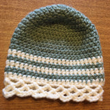 A wool blend crocheted adult hat with stripes and lace details.