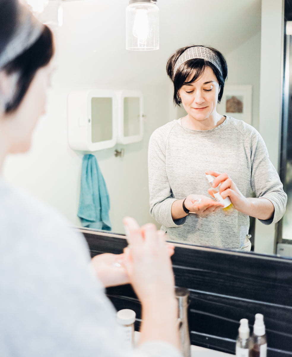 A woman with dark hair and a grey sweater stands in front of a bathroom mirror using skincare.