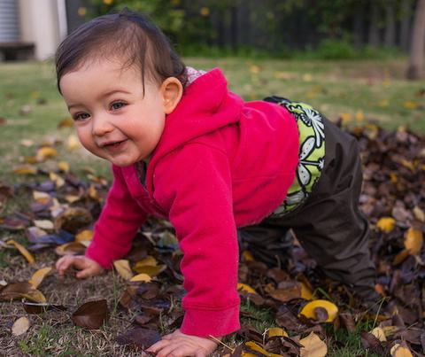 playing in autumn leaves wearing mudbubs