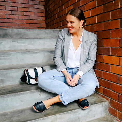 Model sitting on concrete stairs wearing denim mum jeans, white shirt, check blazer, black avarcas