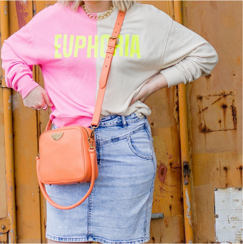 women wearing bright coloured jumper with Euphoria logo and coral coloured cross body handbag