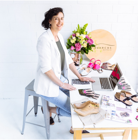 Owner Naomi wearing denim jeans green top and white jacket sitting at a stylised desk with laptop avarcas promotional material