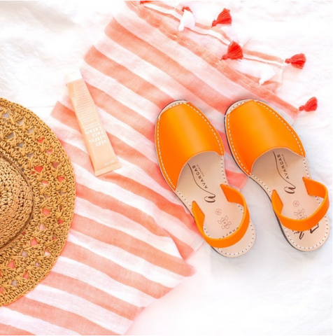 Neon orange avarcas lying on an orange and white striped towel with straw hat