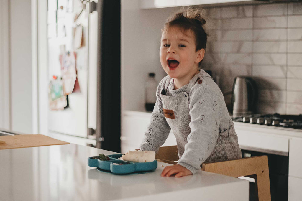 Toddler eating meal at kitchen bench