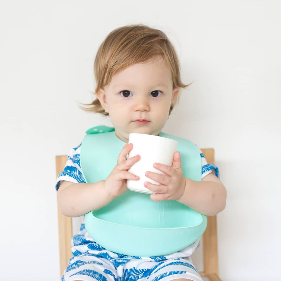 Toddler with mint silicone bib
