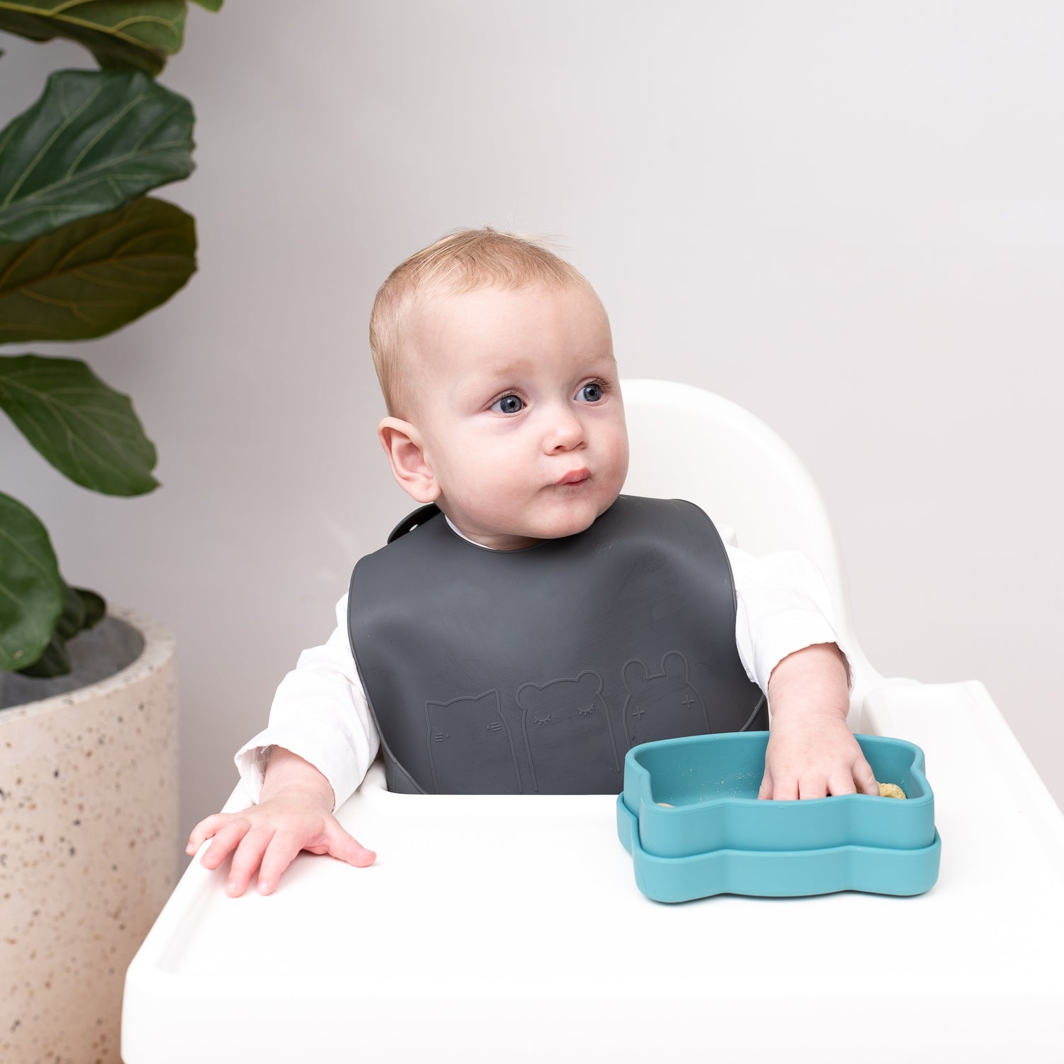 Baby with charcoal silicone bib by We Might Be Tiny