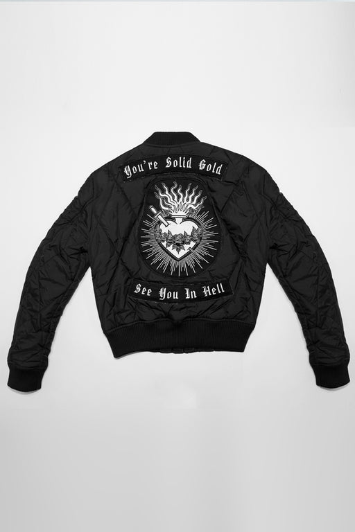 "black quilted cropped bomber jacket with embroidered back patch with sacred heart and ""you're solid gold, see you in hell"""