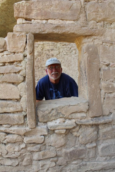 bob at mesa verde looking through a window opening