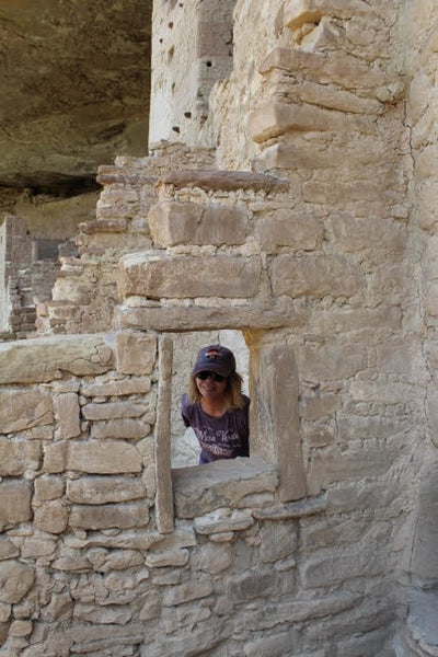 Cathy at mesa verde looking through a window opening