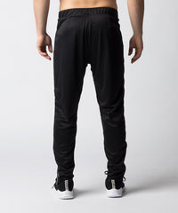 Black, enhanced warm-up pant that has a uniquely constructed knee joint that mimics users legs in motion.  Zippered side pockets allow for secure items and zippered ankles allow for controlled ventilation.