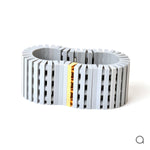 Light grey striped bracelet with goldplated brick