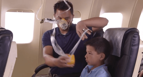 Man helping child put on oxygen mask in airplane
