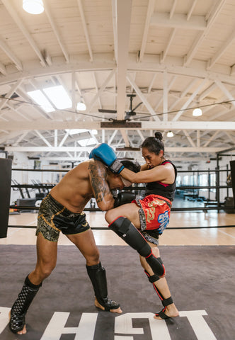 Woman and Man Practicing Muay Thai Sparring in Ring
