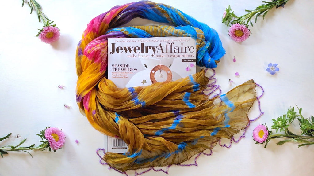 Colorful silk scarf framing Jewelry Affair magazine with featured article