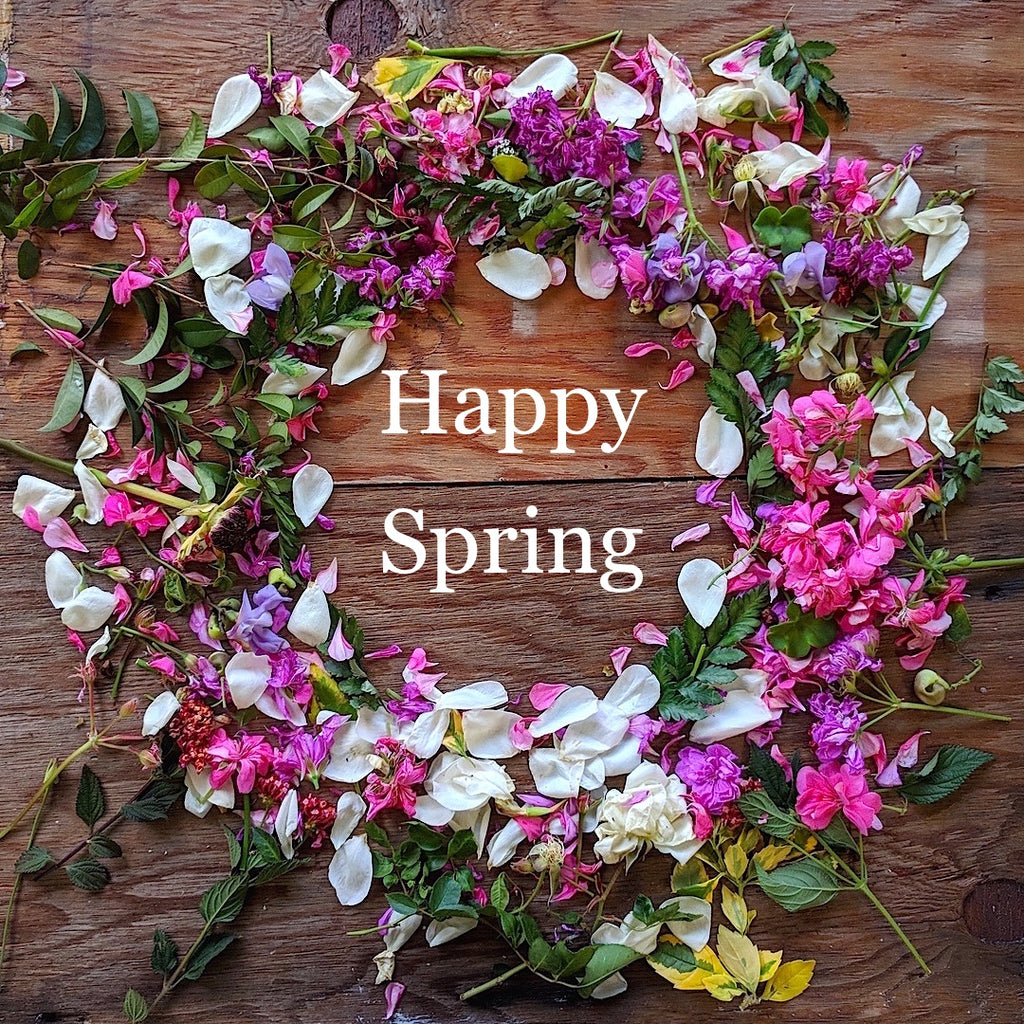 "Wreath of flowers on dark wood background labeled ""Happy Spring"""
