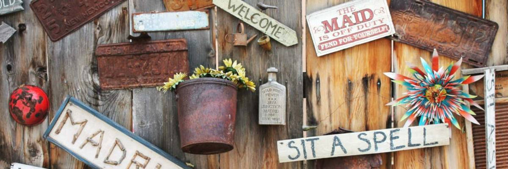 rugged welcome signs and old license plates mounted on wood fence