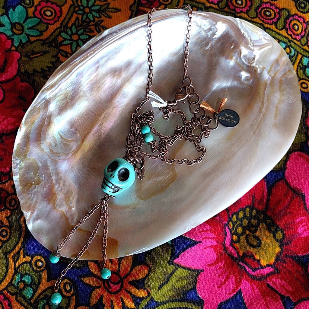 long necklace photographed on top of mother-of-pearl shell