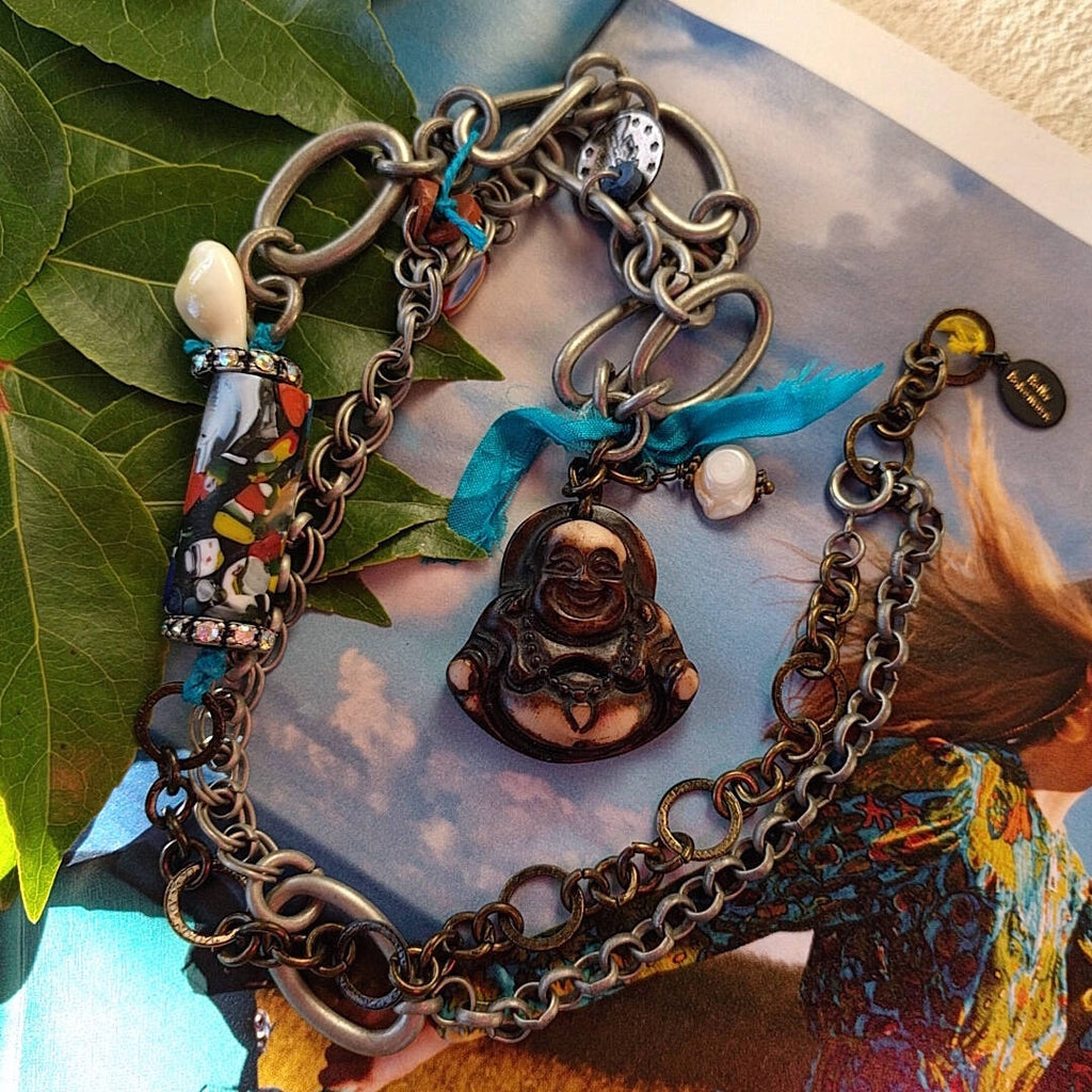 handmade mixed-metal necklace with hand carved happy buddha on top of magazine