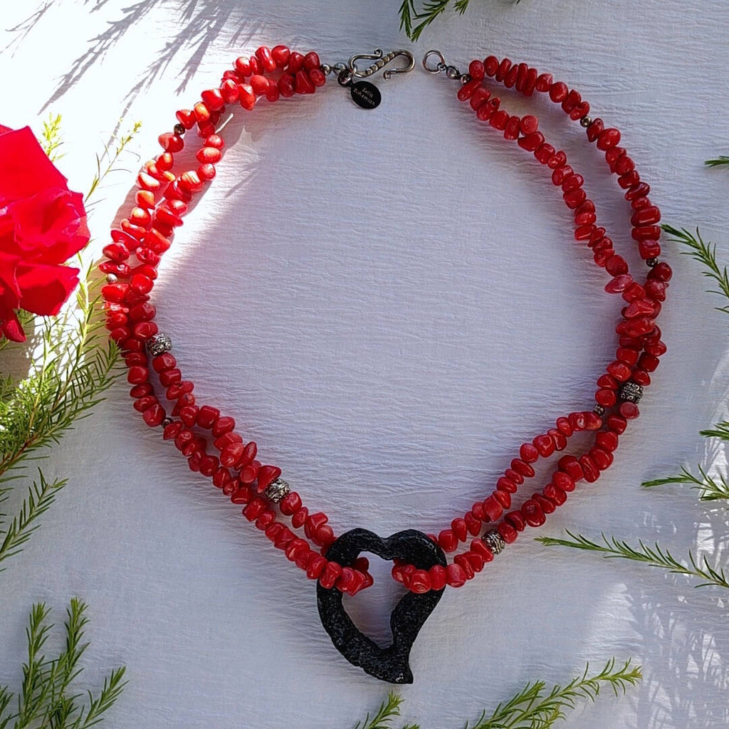 double strand coral necklace with lava heart photographed on plain background