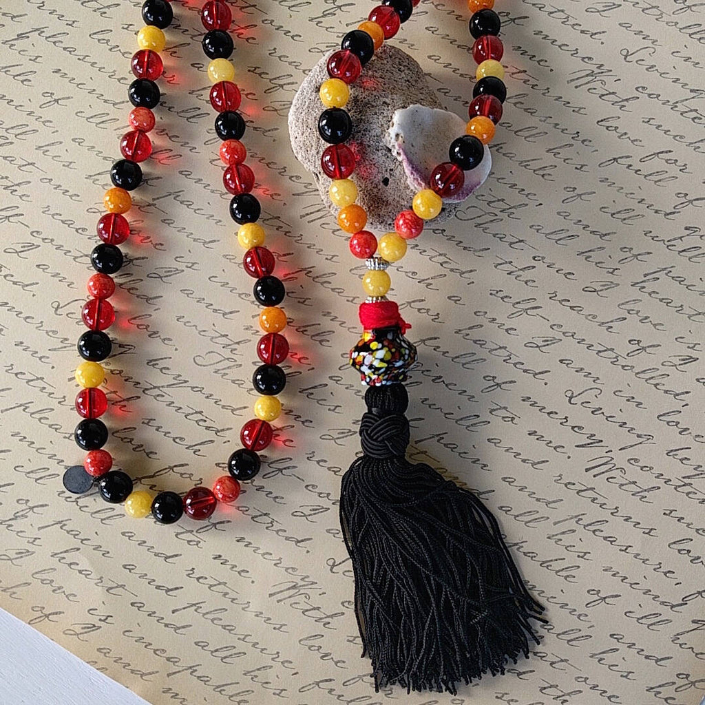 long bohemian style necklace made with color beads tibetan silver waxed cord and a nylon tassel