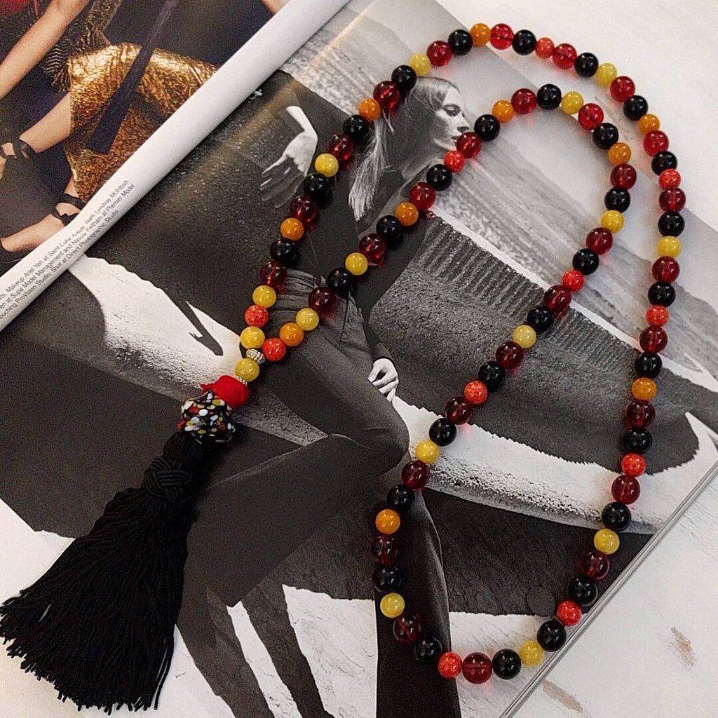 long bohemian style necklace made with various color beads tibetan silver waxed cord and a nylon tassel