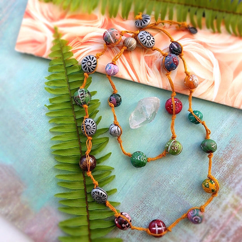 long rustic strand necklace hand-knotted with an orange hemp cord and multi-colored hand carved clay stones