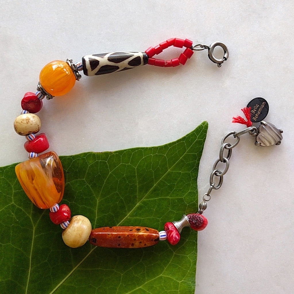 handmade bracelet on black waxed thread with African amber beads, red corals, round ivory bone beads, Ghana colored seed beads, silver-plated caps