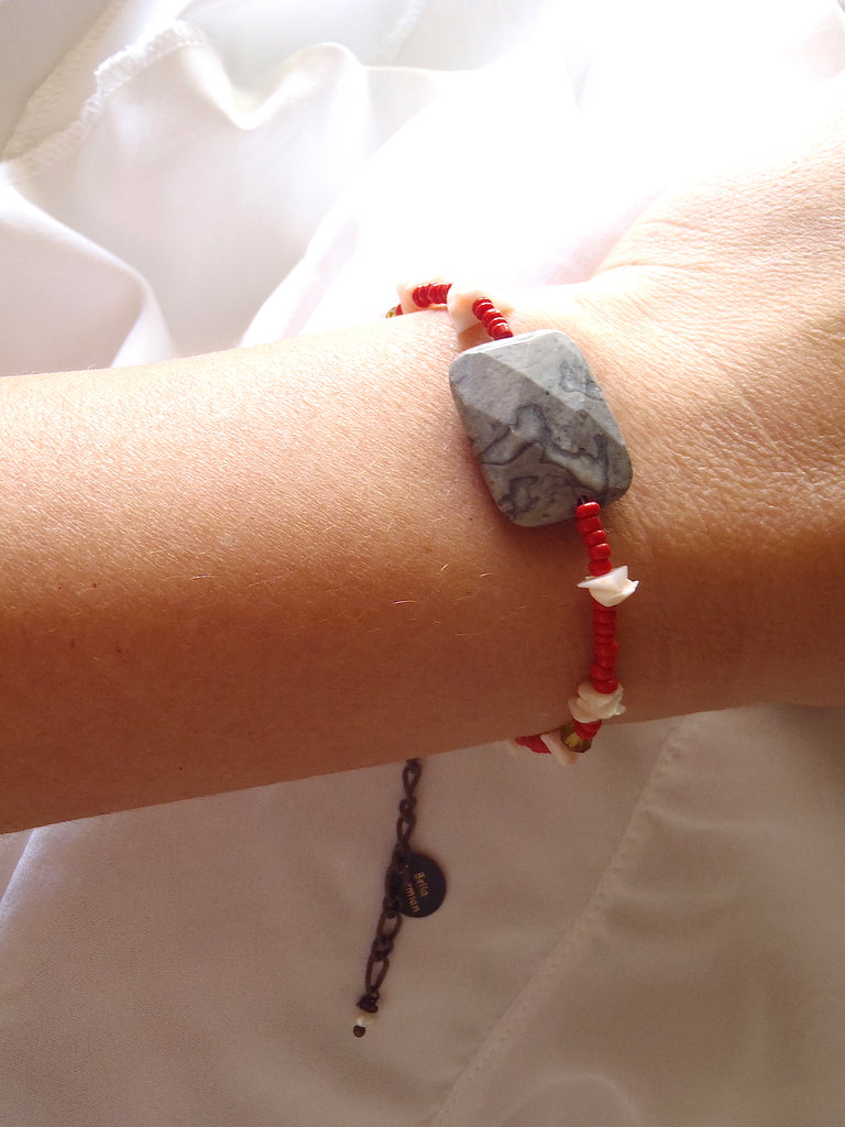 handmade friendship bracelet with red Indian seed beads shown worn on a lady's wrist