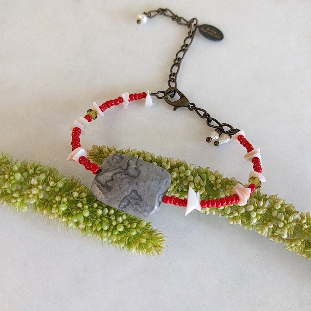 handmade friendship bracelet with red Indian seed beads, white coral chips, tiny green Swarovski beads and lobster clasp