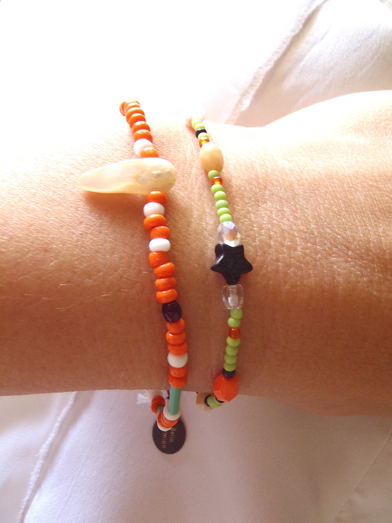 set of 2 handmade bracelets with white, creme and orange glass beads shown on a lady's wrist