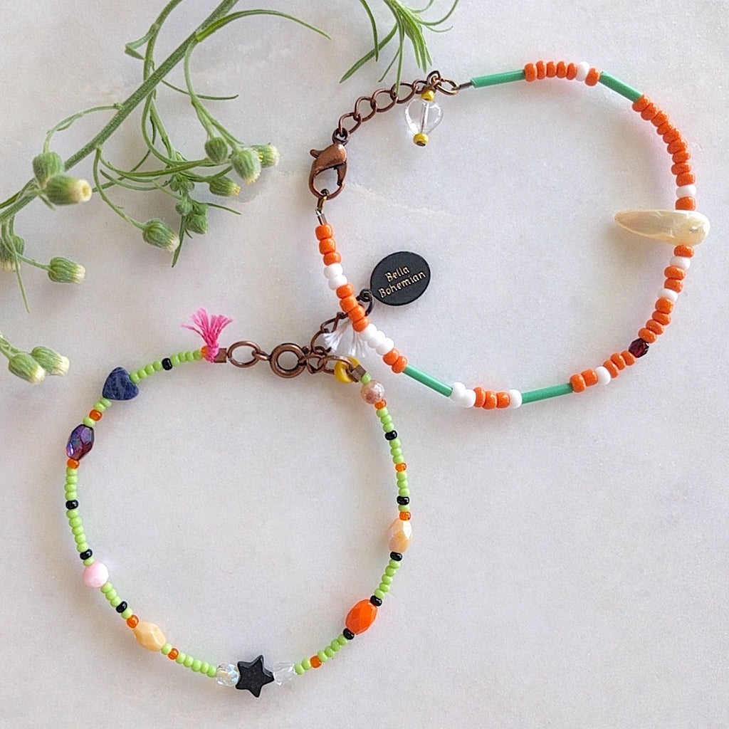 set of 2 handmade bracelets with white, creme and orange glass beads, tiny dark blue heart and tiny black star, lemon green skinny tube, pink tassel