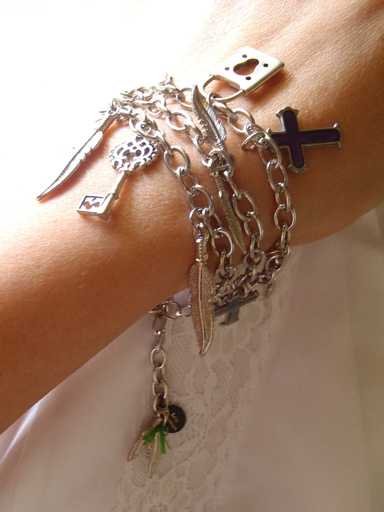 triple chained silver-plated bracelet with cross, feathers, and key charms shown on a lady's wrist