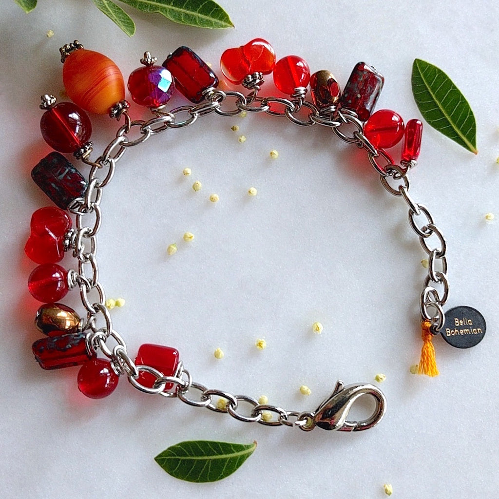 handmade silver-plated charmed bracelet with fire red polished Czech glass beads, and an oval orange matte abstract glass bead center charm