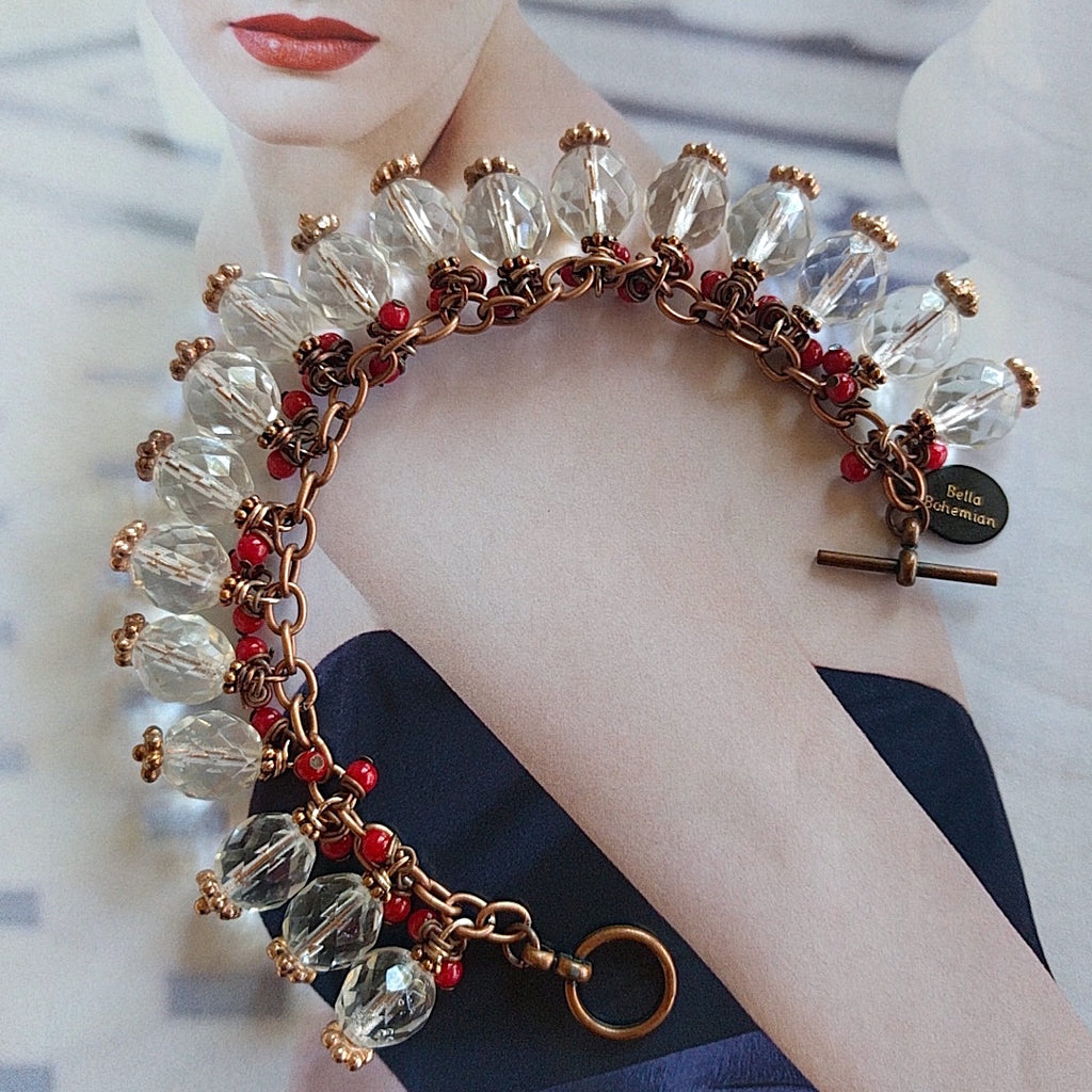 Copper charmed bracelet with red corals and Swarovski crystals on alternate background