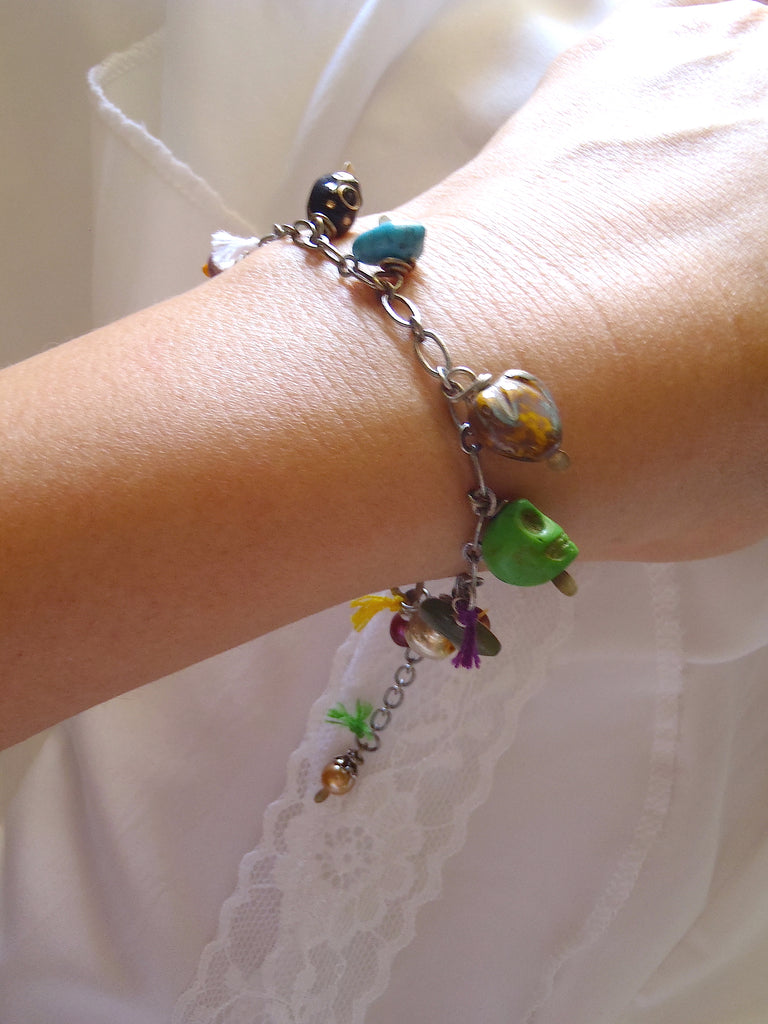 charm bracelet with peacock, burgundy fresh water pearls, jade bear, and green skull shown on a lady's wrist